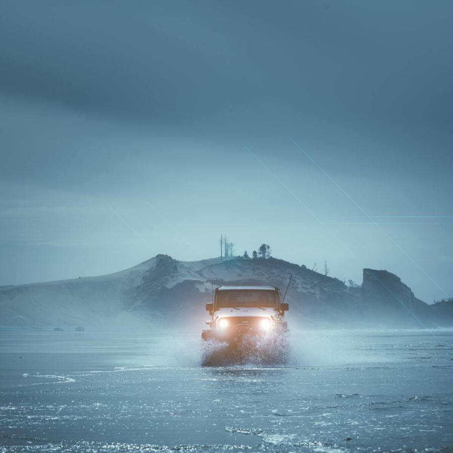 Vehicle driving in foggy wet weather across an icy tundra. Small hill with electronic towers on top in the background. Black, stormy clouds overhead.
